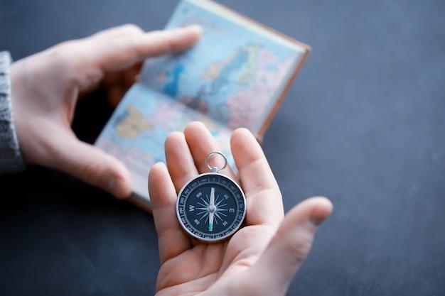 Concetto di viaggio. bussola magnetica in mano. navigatore retrò in mano una mappa e lo sfondo dell'aeroplano. sfondo di avventura.