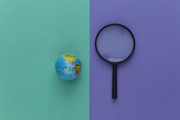 Concetto di viaggio. lente d'ingrandimento con globo su un viola blu