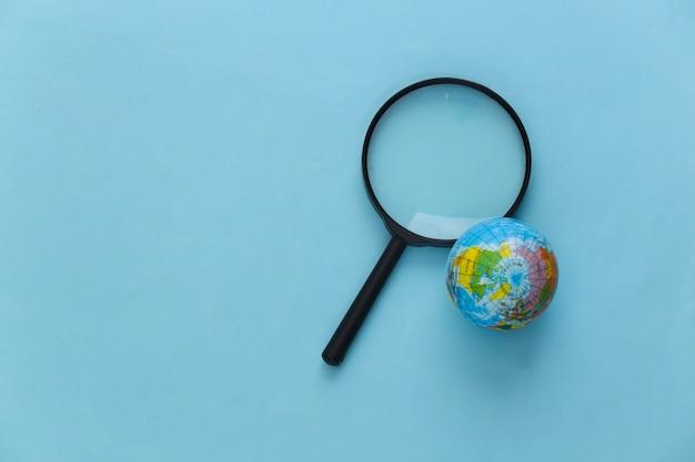 Concetto di viaggio. lente d'ingrandimento con globo su un blu