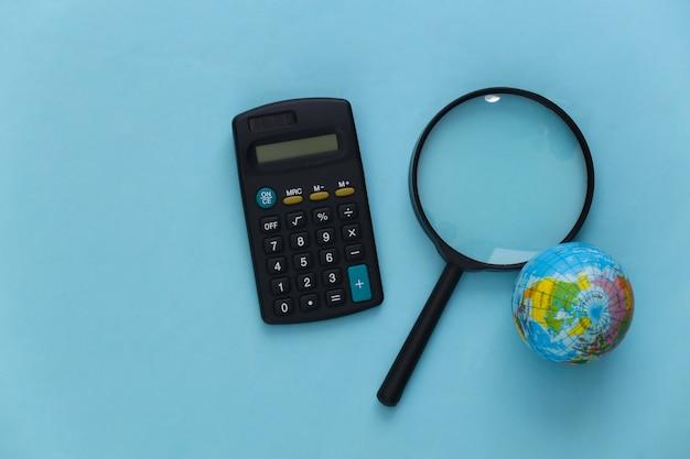 Concetto di viaggio. lente d'ingrandimento con globo e calcolatrice su un blu