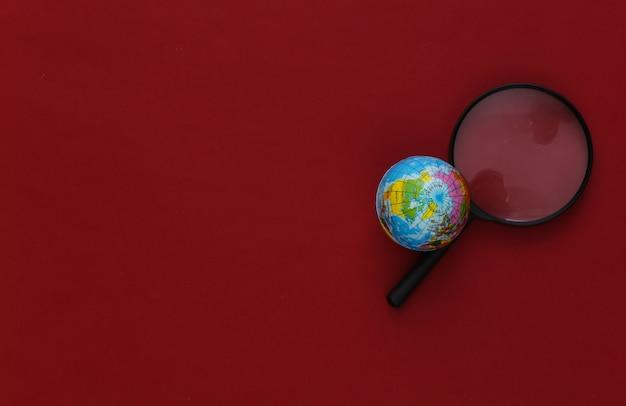 Concetto di viaggio. lente d'ingrandimento con globo su rosso