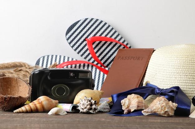 Concetto di viaggio una mappa, macchina fotografica, passaporto e infradito su un tavolo di legno marrone. rilassamento. vacanze