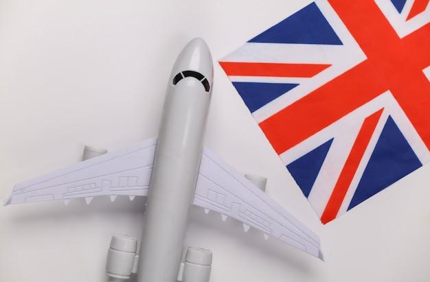 Concetto di viaggio. aereo passeggeri e bandiera britannica su sfondo bianco