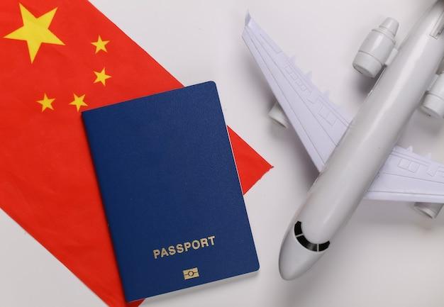 Concetto di viaggio. aereo passeggeri, passaporto e bandiera della cina su sfondo bianco