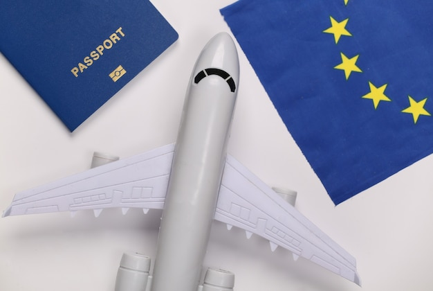 Concetto di viaggio. aereo passeggeri, passaporto e bandiera dell'unione europea su sfondo bianco