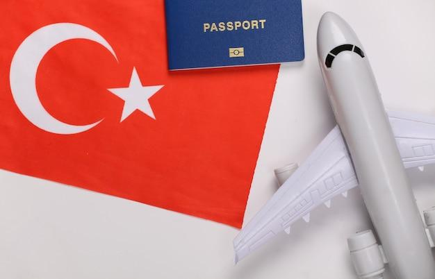 Concetto di viaggio. aereo passeggeri, passaporto e bandiera turca su sfondo bianco