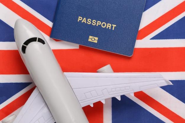 Concetto di viaggio. passaporto e aereo sullo sfondo della bandiera britannica
