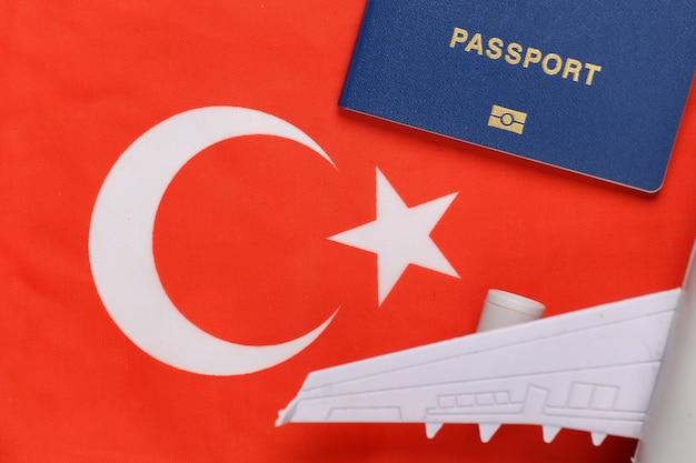 Concetto di viaggio. passaporto e aereo sullo sfondo della bandiera turca