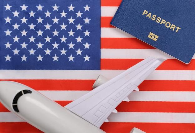 Concetto di viaggio. passaporto e aereo sullo sfondo della bandiera degli stati uniti