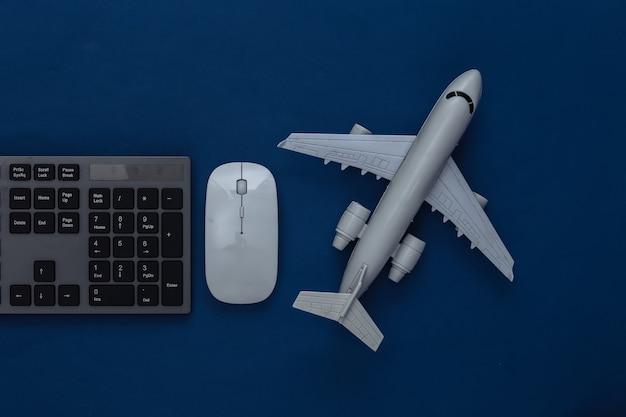 Concetto di viaggio. tastiera pc e aereo su un classico blu