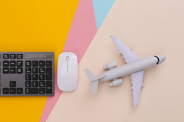 Concetto di viaggio. tastiera pc e aereo su tavola colorata on