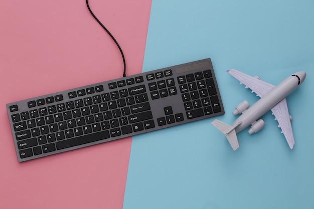 Concetto di viaggio. tastiera del pc e aereo su rosa blu