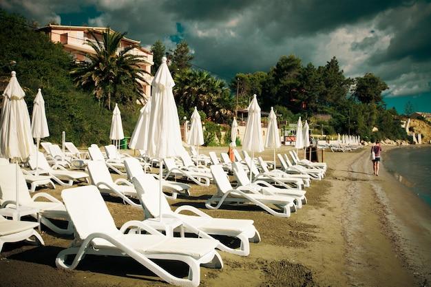 Concetto di viaggio - sedie a sdraio con ombrelloni sulla bellissima spiaggia, isola di zante, grecia