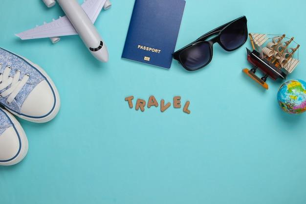 Concetto di viaggio. accessori del viaggiatore su un blu con la parola viaggio. crociera, volo aereo, vacanza flat lay. copia spazio