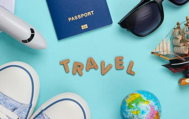 Concetto di viaggio. accessori del viaggiatore su un blu con la parola viaggio. crociera, volo aereo, vacanza flat lay