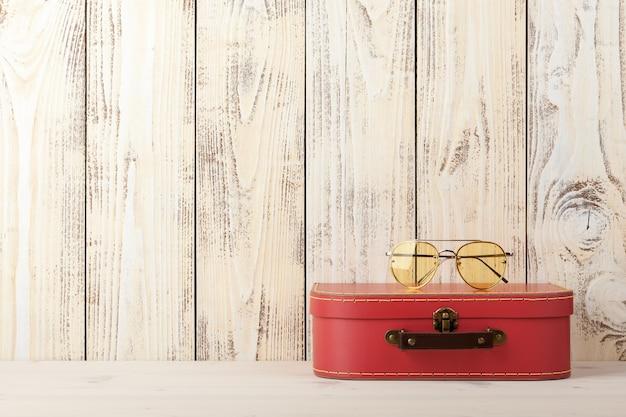Concetto di viaggio con valigia in stile retrò e occhiali da sole