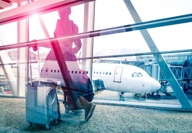 Concetto di viaggio con donna e valigia che si spostano velocemente al cancello del terminal dell'aeroporto - sguardo a doppia esposizione con focus sull'aereo sullo sfondo - chiarore di sole marsala viola con editing filtrato vintage