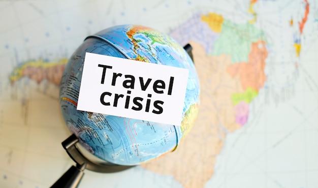Crisi di viaggio - testo su un foglio bianco nel piccolo globo sullo sfondo della mappa dell'atlante