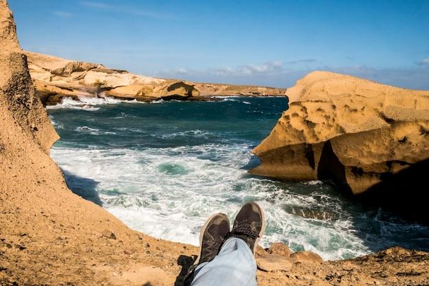 Viaggia e scopri luoghi panoramici concpet per le gambe sdraiati e rilassati su una scogliera con onde oceaniche di tempesta blu grandi e pericolose - colori e attività della costa in vacanza