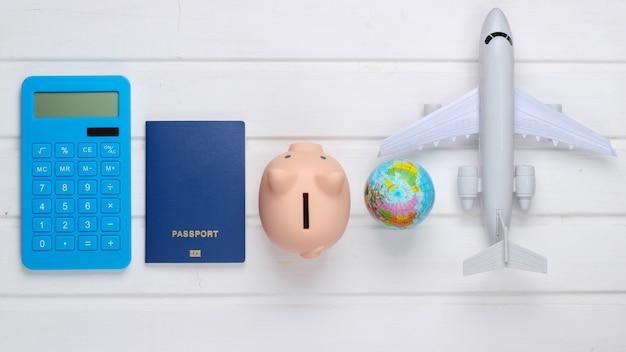 Viaggio o emigrazione. passaporto con salvadanaio, calcolatrice, globo e aereo su superficie di legno bianca. vista dall'alto. lay piatto