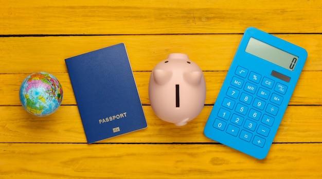 Viaggio o emigrazione. passaporto con salvadanaio, globo e calcolatrice su una superficie di legno gialla. vista dall'alto. lay piatto