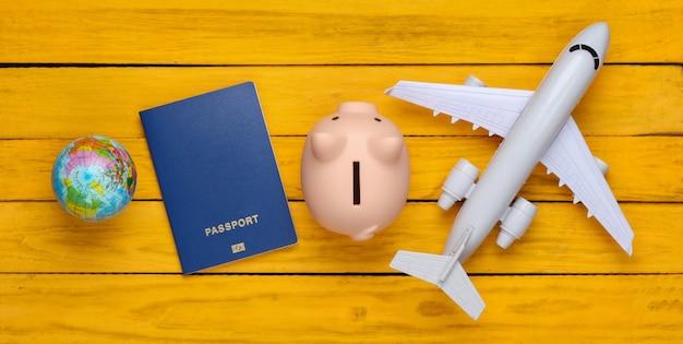 Viaggio o emigrazione. passaporto con salvadanaio, globo e aereo su una superficie di legno gialla. vista dall'alto. lay piatto