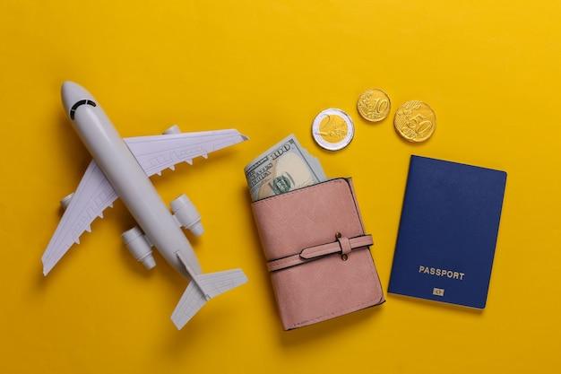 Tema del viaggio o dell'emigrazione. figurina di aereo, portafoglio con soldi, passaporto su un giallo