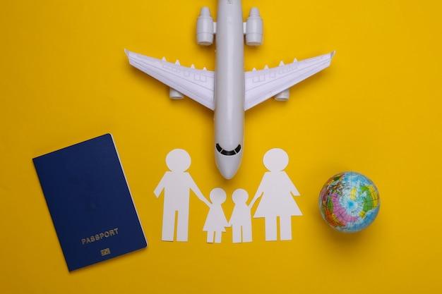 Viaggio o immigrazione familiare. famiglia di carta insieme, aereo, globo e passaporto su giallo.