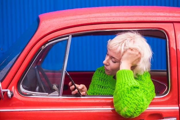 Concetto di viaggio e moda con persone attraenti signora caucasica all'interno di una bella auto retrò rossa utilizzando il telefono cellulare connesso a internet per controllare la mappa e scoprire nuovi posti. immagine a colori.