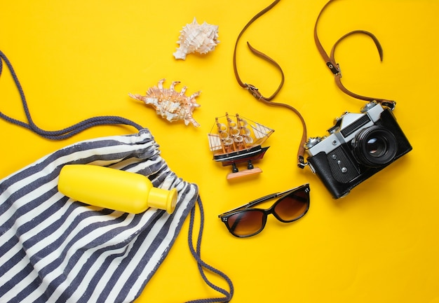 Accessori da viaggio piatti laici e fotocamera retrò su giallo