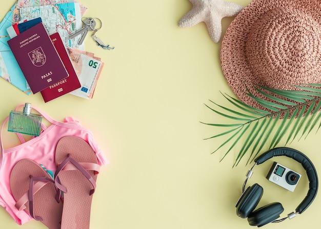 Piatto da viaggio laici con diversi accessori per viaggiare con uno spazio di copia, su uno sfondo giallo