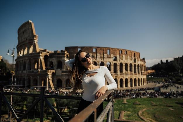 Ragazza di viaggio sorridente e in posa contro il colosseo romano.