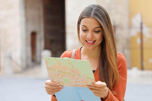 Ragazza di viaggio che visita la città alla ricerca di direzione sulla mappa