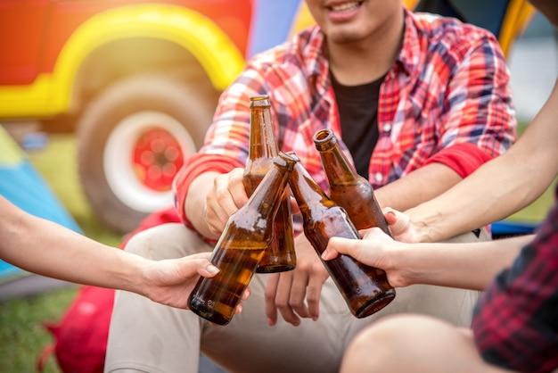 Gruppo di amici di viaggio godetevi camping party e clinking beer bottle in estate