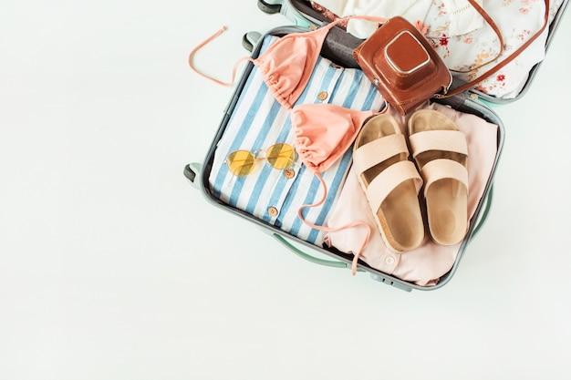 Viaggio bagaglio a mano con bikini costume da bagno, pantofole, occhiali da sole, vestito, fotocamera retrò su bianco. Foto Premium