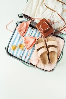 Viaggio bagaglio a mano con bikini costume da bagno, pantofole, occhiali da sole, vestito, fotocamera retrò su bianco.