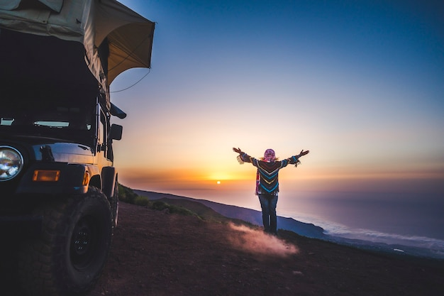 Concetto di viaggio e felicità per persone con voglia di viaggiare - donna con vestiti caldi colorati godersi la libertà e il tramonto vicino a un'auto con tenda sul tetto - indipendenza e stile di vita selvaggio viaggiatore femminile