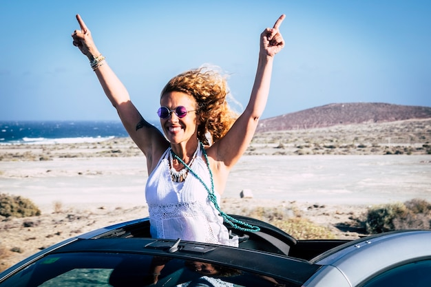 Viaggia e felicità con un'auto decappottabile per una donna adulta allegra e felice che celebra il viaggio di vacanza alternativo vacation
