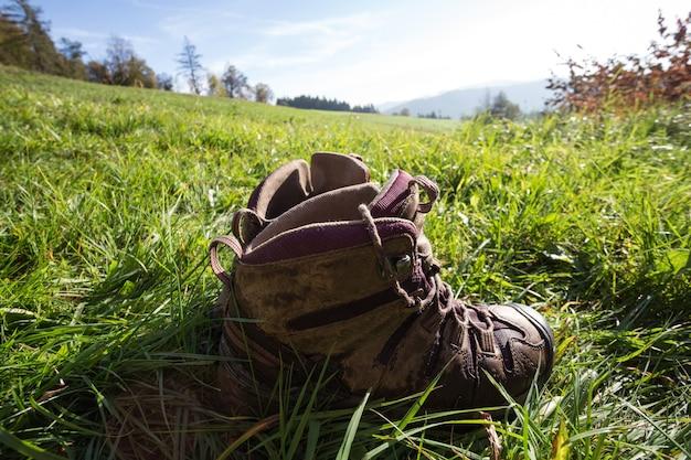 Viaggiare. escursionista che riposa in montagna - stivali sull'erba