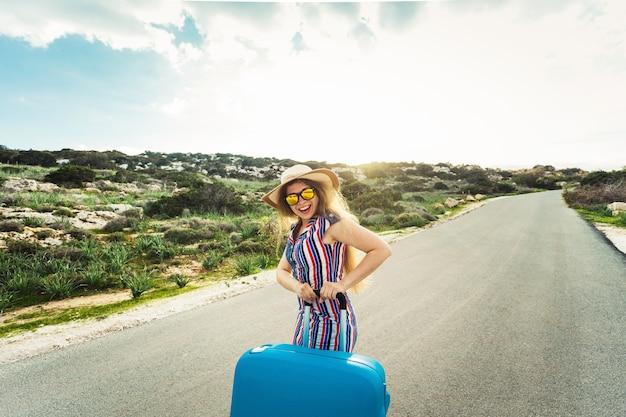 Concetto di viaggio, vacanza, estate e vacanza - la giovane donna affascinante è in piedi e ride per strada con le valigie