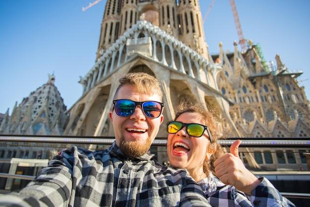 Concetto di viaggio, vacanze e persone - coppia felice che cattura foto selfie a barcellona.