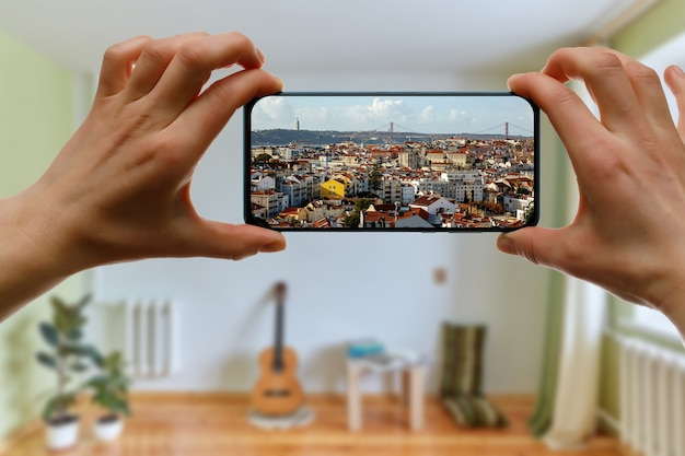 Viaggia a casa. viaggio online a lisbona, portogallo tramite smartphone. cityscape sullo schermo.