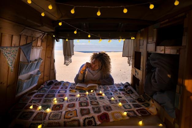 Viaggio e concetto di stile di vita indipendente con giovane bella signora libera riccia che legge un libro fuori dal suo furgone in legno vintage fatto a mano e spiaggia soleggiata sabbiosa all'aperto in scena