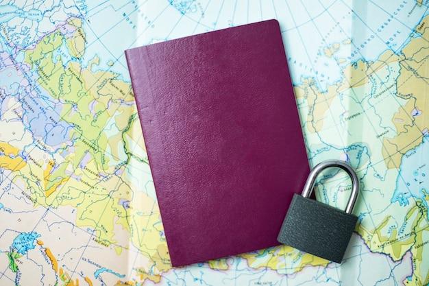 Concetto di divieto di viaggio. mappa, passaporto e mano con lucchetto.