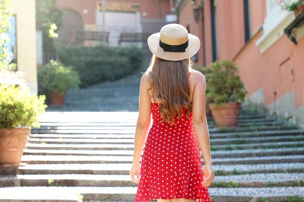 Viaggio in italia. vista posteriore della ragazza turistica sale le scale a bellagio, italia. donna giovane viaggiatore durante le sue vacanze estive sul lago di como, europa meridionale.