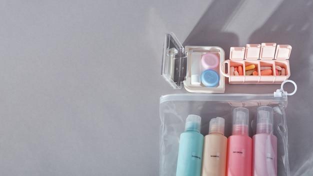 Kit da viaggio. set di quattro piccole bottiglie di plastica per prodotti cosmetici in busta trasparente, kit per lenti a contatto, organizer per pillole. sfondo grigio con ombre.
