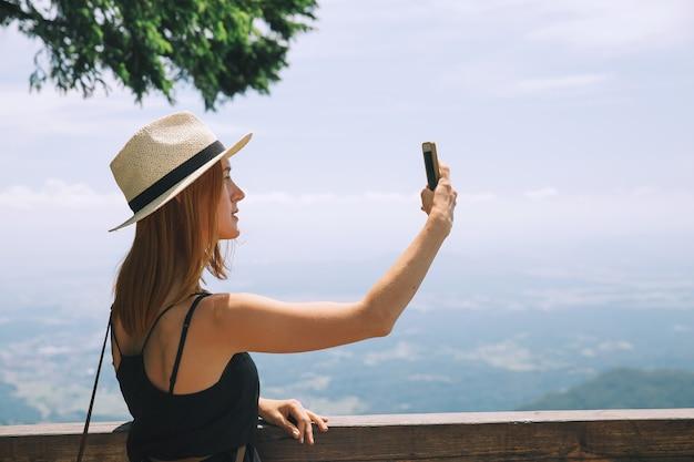Viaggi, concetto di stile di vita. il viaggiatore scatta foto su un telefono cellulare in montagna.