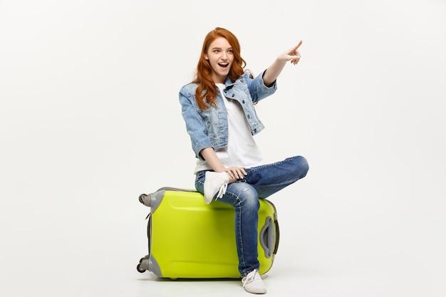Concetto di viaggio e stile di vita: giovane donna caucasica seduta su una valigia e che indica la direzione dove andare.