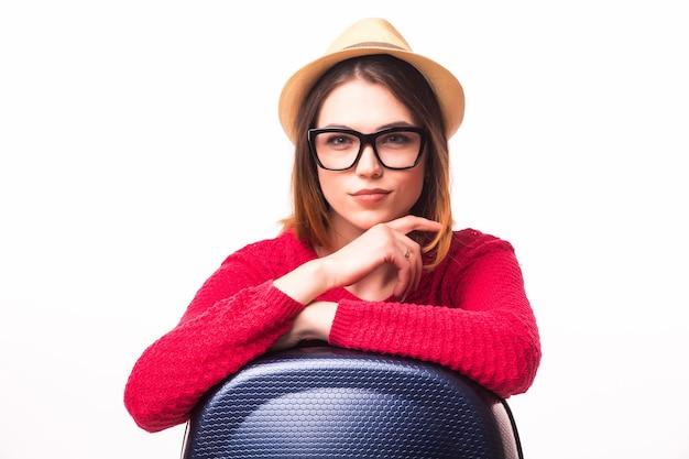 Concetto di viaggio e stile di vita. giovane donna con la valigia pronta per il viaggio estivo isolato sul muro bianco
