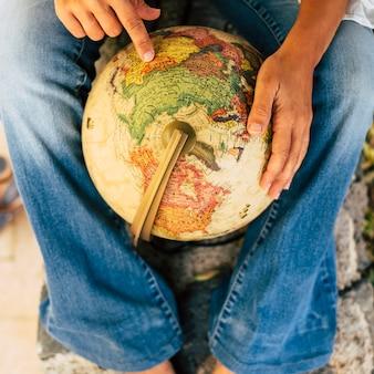 Concetto di stile di vita di viaggio - primo piano di una donna irriconoscibile che sceglie la prossima destinazione su una mappa del mondo